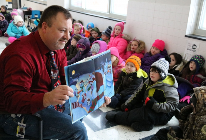 "Sandy Creek Elementary School Principal Tim Filiatrault reads ""Snowmen at Night"" to the first grade classes before going outside to make their own snowmen."